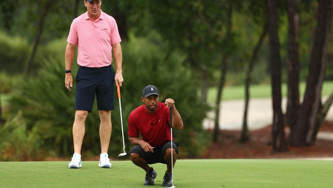 Tiger Woods and former NFL player Peyton Manning read a putt on the sixth green during The Match: Champions for Charity at the Medalist Golf Club on Sunday in Hobe Sound.