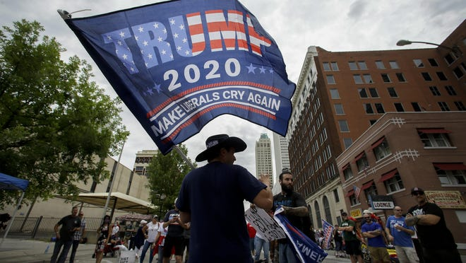 A supporter waves a flag June 20 prior to a campaign rally for President Trump at the BOK Center in Tulsa, Oklahoma. A new poll from The Associated Press-NORC Center for Public Affairs Research finds that Joe Biden's supporters are less enthusiastic than President Donald Trump's, both about the campaign itself and their candidate.