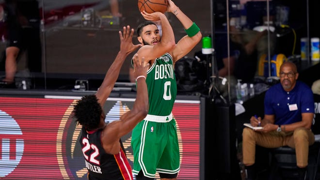 Miami Heat forward Jimmy Butler (22) defends as Boston Celtics forward Jayson Tatum (0) goes up for a shot during the second half of Game 4 of an NBA basketball Eastern Conference final, Wednesday, Sept. 23, 2020, in Lake Buena Vista, Fla.