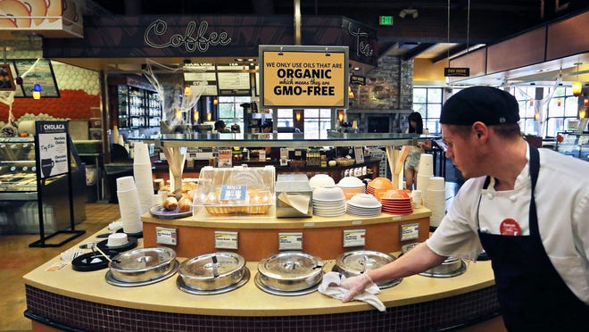 In this 2014 photo, a grocery store employee wipes down a soup bar with a display informing customers of organic, GMO-free oils, in Boulder, Colo.