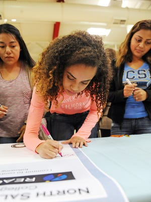 North High senior Kori Fletcher is first to sign in to the University of California's table at the high school's College Signing Day on Tuesday in Salinas.