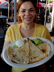 Cheese Quesadillas are displayed by Julissa Lopez, owner of Bad Ass Street Tacos