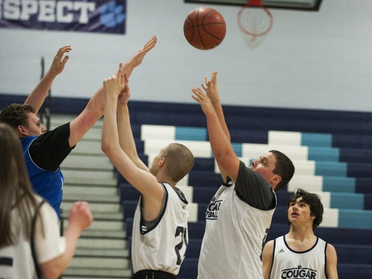A Mount Mansfield player shoots the ball during a basketball