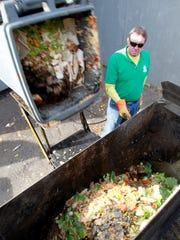 In this Nov. 15, 2013, photo, Bob Freeman loads food scraps from the Wayside Restaurant  in Berlin, Vt. Vermont has taken another step toward its ambitious goal of mandating statewide recycling, including the composting of food scraps, by creating universal symbols that will be used on trucks and containers for recycling, food scraps and trash.The law passed by the Legislature last year requires statewide recycling by 2015 and keeping food scraps out of landfills by 2020.