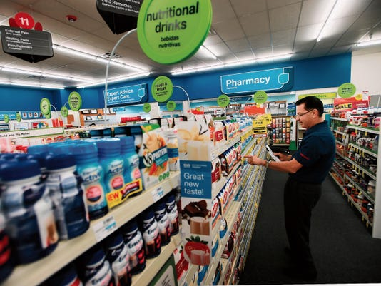 VICTOR CALZADA-EL PASO TIMES Gilberto Chaparro prepared a display last week at the CVS/pharmacy store at 1212 McRae. A shopping center was demolished to make way for the drugstore, which opened last August.