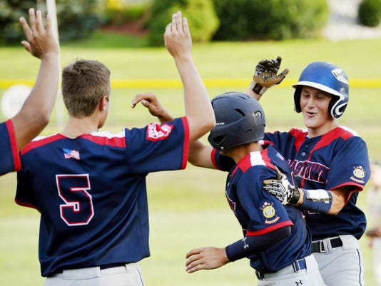 Dallastown's Regis Maher (5) and Chase Miller, center, congratulate teammate Nick Schuler after Miller scored the winning run on Schuler's sixth-inning hit during Friday's American Legion baseball tournament first-round game at Shryock Field in York Township. Dallastown won, 11-1, to advance to Sunday's semifinal against Northeastern.