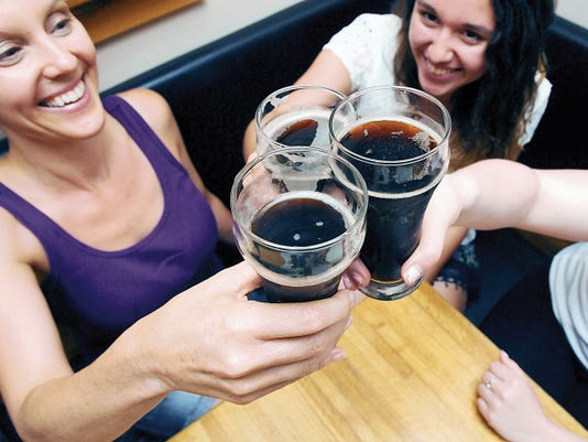 "Robin Zielinski   Sun-NewsApril Sexton, left, Emma Sexton, right, and Noalani Mirsch (not pictured), of Eugene, Oregon, raise and touch their glasses on Tuesday at High Desert Brewing. ""We are from out of town and came specifically for the root beer and nachos,"" said Sexton."