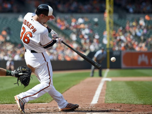 Baltimore's Caleb Joseph hits a single against during the fifth inning of Sunday's game against the Oakland Athletics in Baltimore. The Orioles won, 18-2.