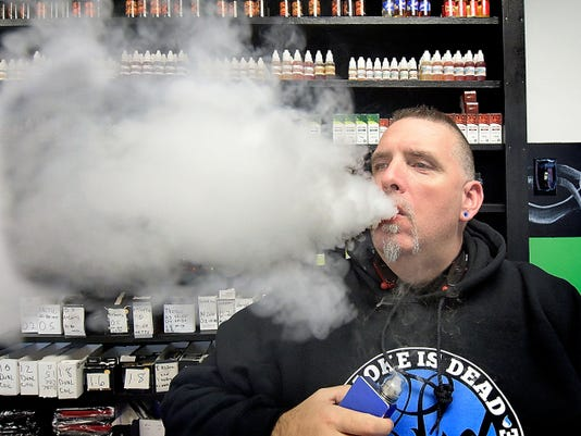LifeSmoke Vapors associate Rick Templin exhales vapor in the Springettsbury Township shop Wednesday. He says the company strictly enforces age requirements for purchases and access to the shop.