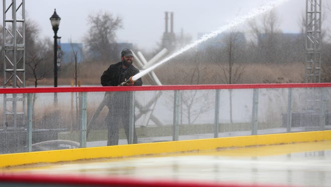 Tex Varney, a production manager for New Castle-based Light Action Productions, sprays water onto the Riverfront Rink in Wilmington earlier this week.