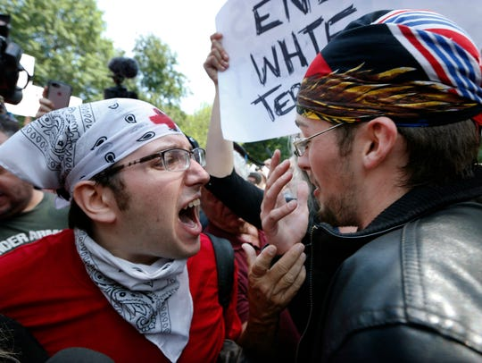 A counter-protester, left, confronts a professed supporter