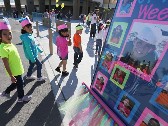 Desert View Elementary School students walk past a poster board which had pictures of Braden Aboud and the school's students of the week.