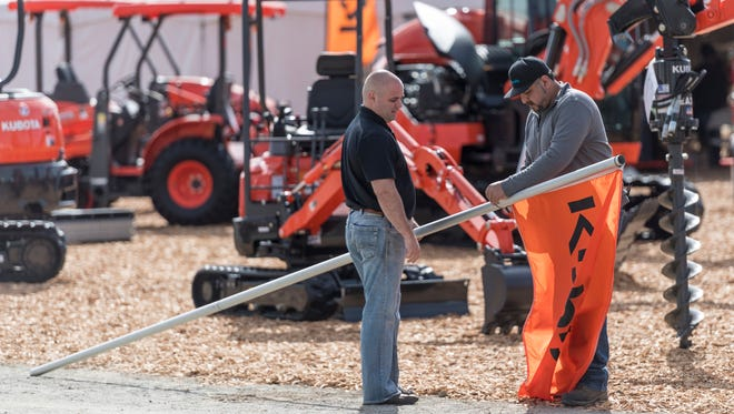 Steve Americano, right, and Brad Preston raise Kubota flags for display during World Ag Expo at the International Agri-Center in Tulare on Monday, February 12, 2018.