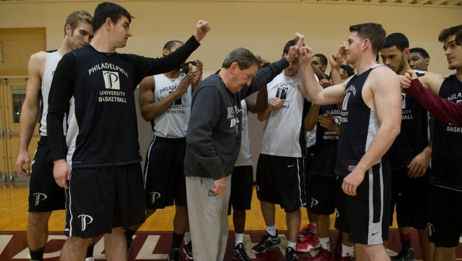 Philadelphia University men's basketball coach Herb Magee huddles with his players at the start of practice at Gallagher Center at Philadelphia University.