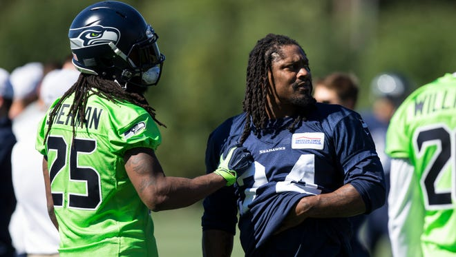 Seattle Seahawks runningback Marshawn Lynch, center, talks with defensive back Richard Sherman (25) during NFL football training camp on Friday, July 31, 2015, in Renton, Wash.
