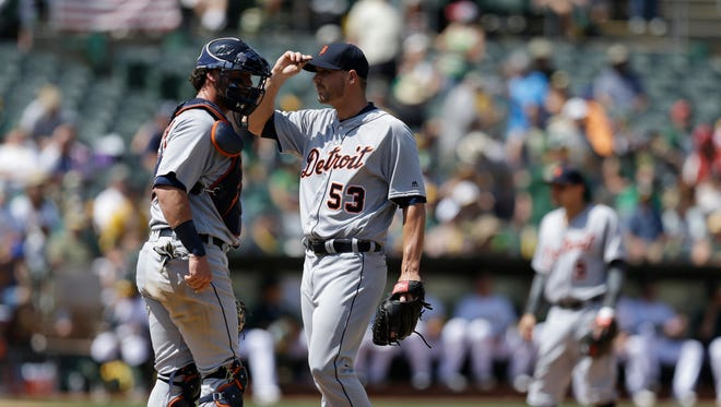 Detroit Tigers' pitcher Warwick Saupold, right, speaks with catcher Jarrod Saltalamacchia in the sixth inning of a baseball game against the Oakland Athletics, Saturday, May 28, 2016, in Oakland, Calif.