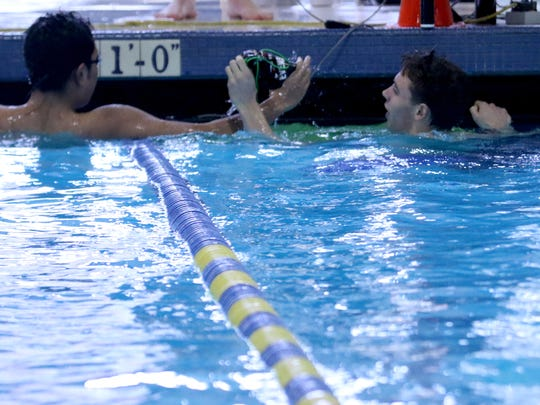 South Salem's Daisuke Fitial, left, and Sprague's Colby Evenson shake hands after competing in the 200 yard individual medley during the Greater Valley Conference swimming championships at the McMinnville Aquatic Center on Saturday, Feb. 11, 2017.
