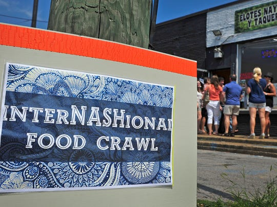 Participants in the 3rd Annual InterNASHional Food Crawl line up to enter a Mexican restaurant called 'Elotes Nayarit y Taqueria.'