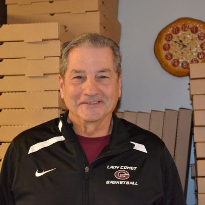 Mike DeStazio stands next to stacks of pizza boxes