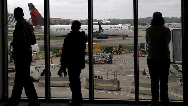 Delta Air Lines passengers watch as a plane taxis at Atlanta's Hartsfield International Airport on April 14.