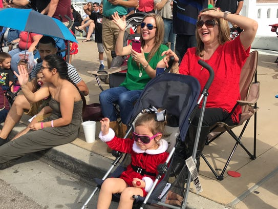 Families cheer and wave as floats from the Children's