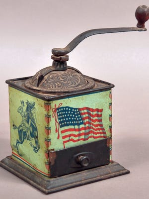 This 10 1/2-inch-high patriotic coffee mill with chromolithographed pictures of President Teddy Roosevelt on the tin sides was made by Bronson-Walton Co. of Cleveland, Ohio. It probably was made in about 1900.