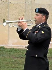 """A bugler plays """"Taps"""" during a ceremony April 10, 2015,"""