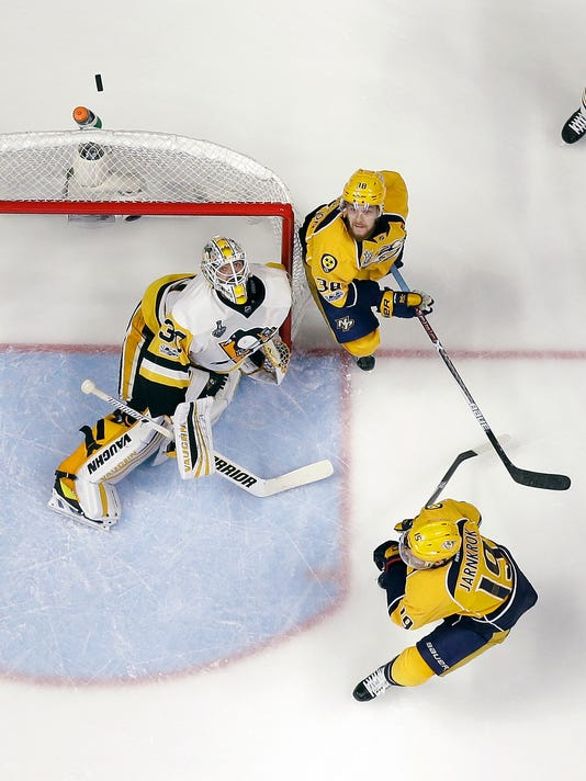 Pittsburgh Penguins goalie Matt Murray (30), and Nashville Predators' Viktor Arvidsson (38), of Sweden, the puck in the air during the third period of Game 6 of the NHL hockey Stanley Cup Final, Sunday, June 11, 2017, in Nashville, Tenn. (AP Photo/Mark Humphrey)