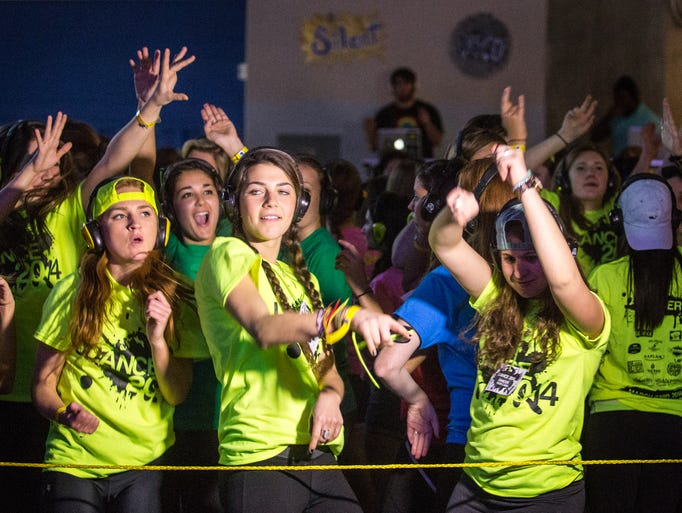 Lisa Finfrock, left, Alexa Dorfman, center, and Talia Rave, right, dance in the silent disco at the UDance dance marathon held at the Bob Carpenter Center in Newark on Sunday. Dancers at the Silent Disco danced to music only they could hear through headphones, coming from one of multiple DJs, leaving everyone dancing to their own beat.