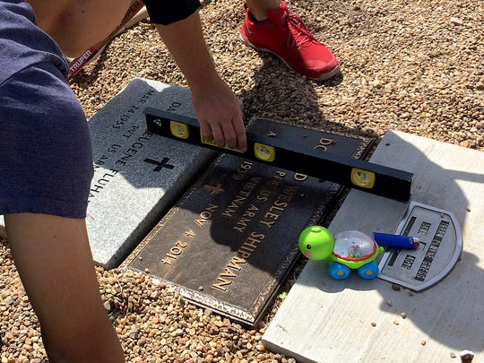 Several Wichita Falls teens and adults work in the Wichita County Cemetery Saturday afternoon to improve the grave markers for area veterans.