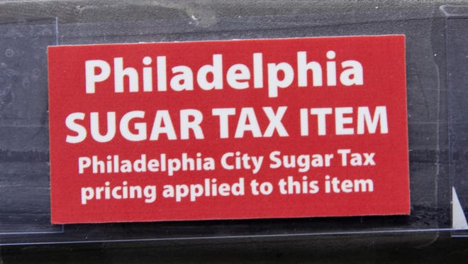 This March 16, 2017 photo shows a sticker alerting customers of the sugar tax posted by sweetened beverages at the IGA supermarket in the Port Richmond neighborhood of Philadelphia. Less than three months into Philadelphia's new tax on sweetened drinks, the stakes have escalated: Beverage makers say the measure is hurting sales so much they need to cut jobs, while city officials say the moves are a ploy to get the tax struck down. (AP Photo/Matt Rourke)