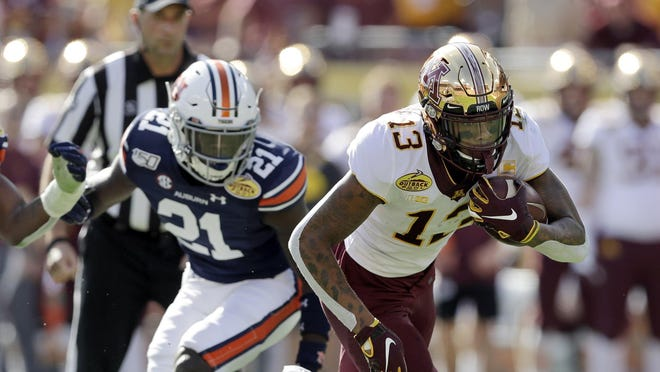 Minnesota wide receiver Rashod Bateman (13) misses a tackle by Auburn defensive back Smoke Monday (21) and defensive end Big Kat Bryant during the first half of the Outback Bowl NCAA college football game Wednesday, Jan. 1, 2020, in Tampa, Fla.