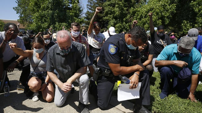Sacramento Sacramento Police Chief Daniel Hahn, foreground right, kneels with others for a moment of silence at a rally in honor of George Floyd, on June 3. Hahn is among the state's Black police chiefs calling for changing state law so they can immediately fire officers for egregious behavior.