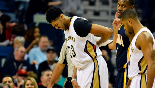 New Orleans Pelicans forward Anthony Davis (23) holds his back after diving out of bounds and into the stands during the first quarter of the game against the Indiana Pacers at the Smoothie King Center.