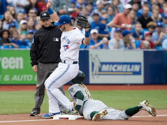 Toronto Blue Jays Josh Donaldson tries to avoid Oakland Athletics Rajai Davis' sliding as Davis tried to steal third during the first inning of a baseball game in Toronto, Monday, July 24, 2017. Third base umpire Will Little called out the steal attempt. (Fred Thornhill/The Canadian Press via AP)