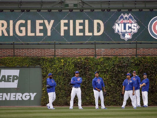Some Chicago Cubs players wait in the outfield at Wrigley Field before Game 4 of the National League baseball championship series against the New York Mets Wednesday, Oct. 21, 2015, in Chicago. (AP Photo/David Goldman)