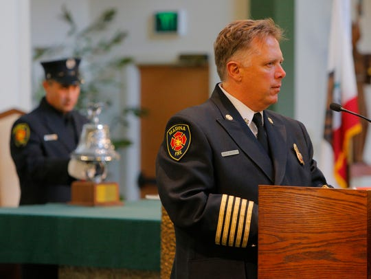 Marina Fire Chief Doug McCoun reads the names of the