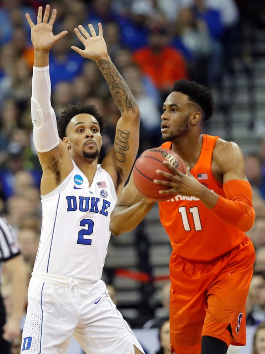 Syracuse's Oshae Brissett (11) passes as Duke's Gary Trent Jr. (2) defends during the first half of a regional semifinal game in the NCAA men's college basketball tournament Friday, March 23, 2018, in Omaha, Neb. (AP Photo/Charlie Neibergall)