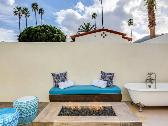 """An outdoor """"soaking tub"""" and fire-pit on the private outdoor patio accompanying one of the 18 restored bungalows at La Serena Villas in Palm Springs."""