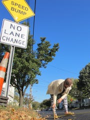 Genevieve Jacobs measures the rise of a speed bump Monday near her house on North Champlain Street in Burlington.