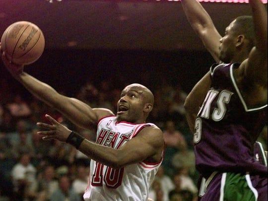 Miami Heat's Tim Hardaway, left, ducks under Milwaukee Bucks' Glenn Robinson to score in 1997. Hardaway has been on both sides of some wild first-round playoff upsets.