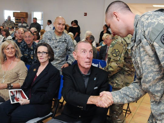 Staff Sgt. Anthony Merino, right, shakes the hand of