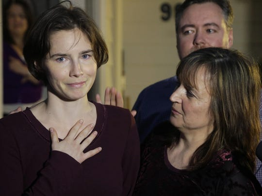 In this 2015 file photo, Amanda Knox, left, talks to reporters as her mother, Edda Mellas, right, looks on outside Mellas' home in Seattle.