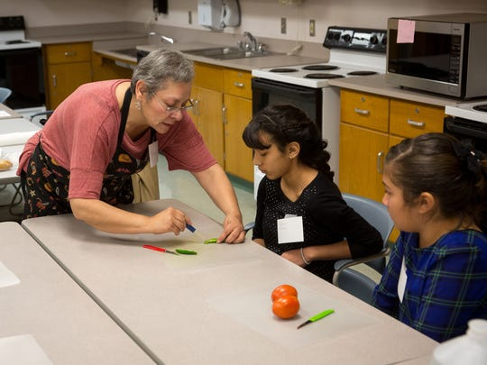Teacher Wendy Maria Harvey, left, demonstrates food preparation techniques to 11-year-old Genesis Ibarra and 12-year-old Danielle Benavidez as part of the Doña Ana Community College Community Education Education course Healthy Cooking for Kids.
