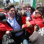 CBS network reporter Carter Evans struggles with security personnel who prevented him from working his way in front of the protesters at Republican presidential candidate Donald Trump's campaign rally at the Convention Center on May 27, 2016, in San Diego.