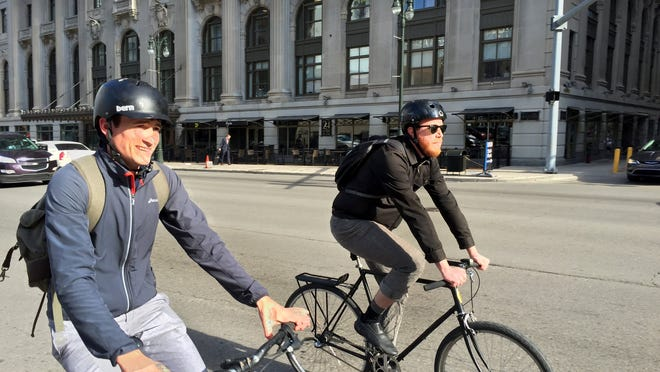 Architects Nate Jenkins, 26, and Josh Maddox, bike on Thursday to their jobs in the Guardian Building.