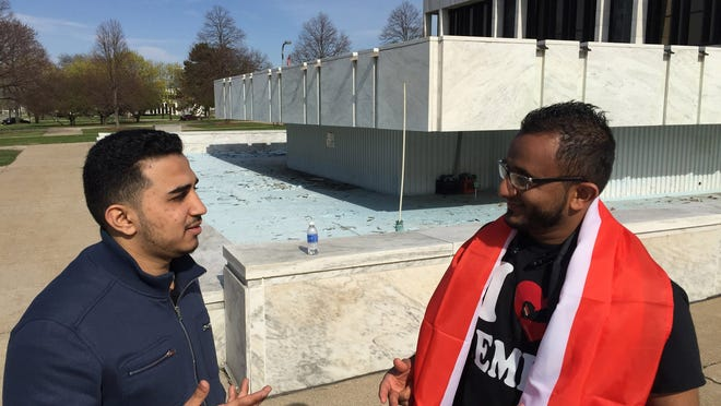 Ismail Mussed of Dearborn, left, talks with Mahmoud Ali of Dearborn outside the library after a rally on April 25 that showed support for actions against the rebels.