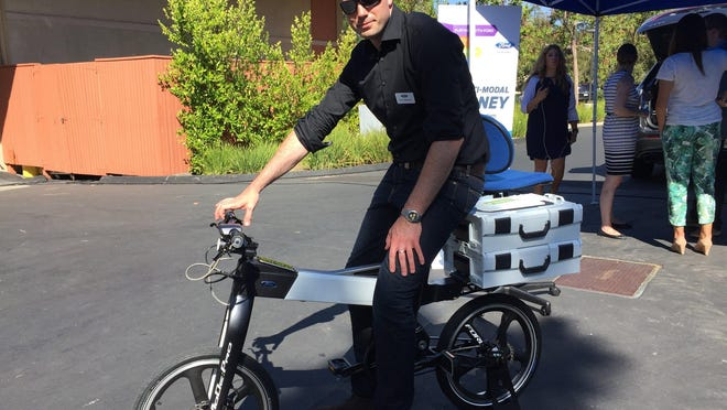 Tom Thompson, a Ford powertrain engineer from the U.K., rides on the MoDe:Pro commercial electric bike he invented.