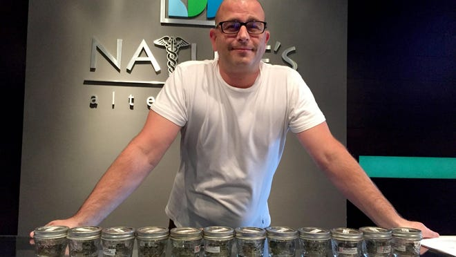 Adam Macdonald, 41, of Grosse Pointe Farms stands Thursday, behind the counter of Nature's Alternative, a medical-marijuana dispensary.