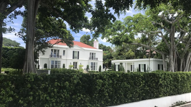 Viewed from the Lake Trail, the west side of the house at 8 S. Lake Trail in Palm Beach faces formal gardens, with windows and French doors offering views of the Intracoastal Waterway and the West Palm Beach skyline. The renovated estate just sold for a recorded $71.85, a new lakefront sales record in Palm Beach.